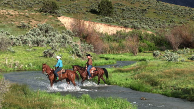 Cowboys Riding Through River in Utah