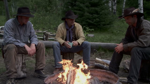 cowboys sit around a fire at dusk - cowboy stock videos & royalty-free footage
