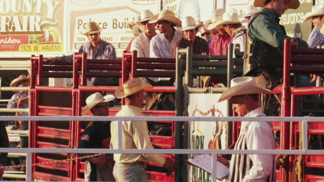 cowboys sit on fences and wait near horse chutes at a rodeo - shot in slow motion. - 1 minute or greater stock videos & royalty-free footage