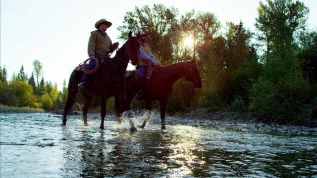 Cowboys with horses in forest river wilderness Canada
