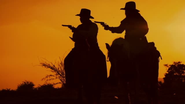 cowboys with revolver riding horses - west direction stock videos & royalty-free footage