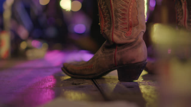 cu. cowgirl guitarist taps her cowboy boots as she performs for an excited crowd at a popular music festival - guitarist stock videos & royalty-free footage