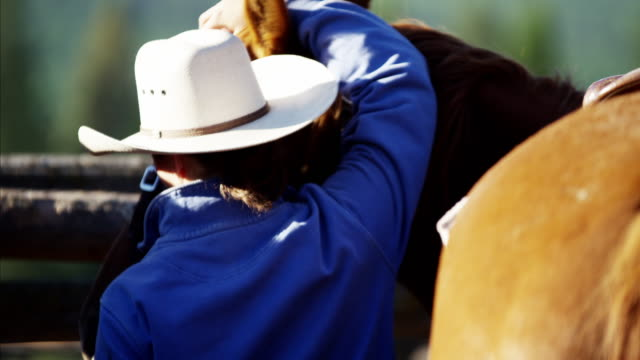 Cowgirl in corral saddling horse Dude Ranch Canada