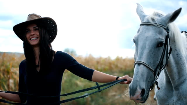 cowgirl is with her white horse - montare video stock e b–roll