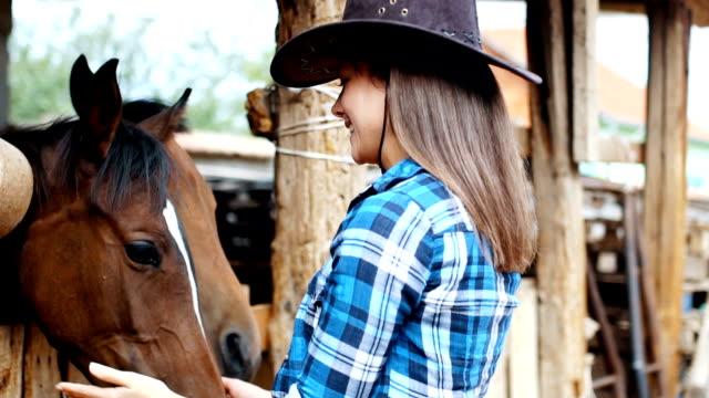 Vaquera besa a su caballo en un establo