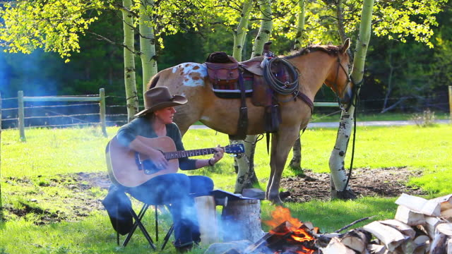 cowgirl playing guitar around campfire with horse - country and western stock videos and b-roll footage