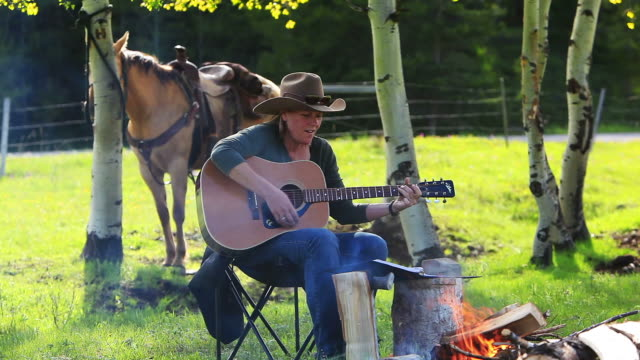 cowgirl playing guitar around campfire with horse - country and western stock videos & royalty-free footage