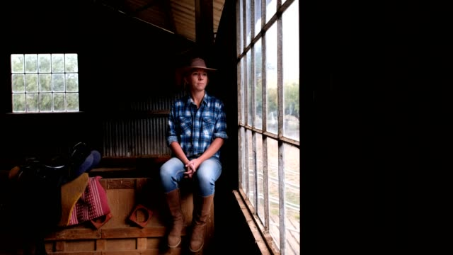 cowgirl sitting in the barn looking out the window - rancher stock videos & royalty-free footage
