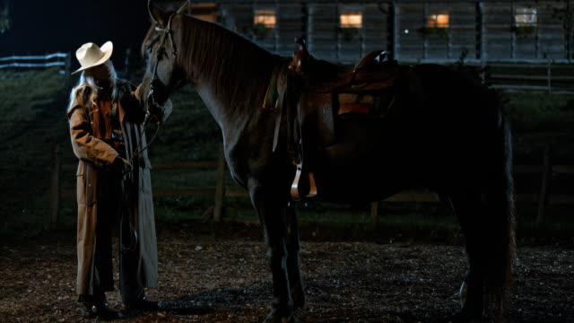 SLO MO DS Cowgirl stroking her horse at night