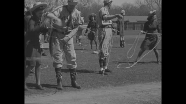 cowgirls exhibit lasso and lariat skills at st louis browns' spring training camp in san antonio tx / girls and players lassoing themselves and each... - spring training stock videos & royalty-free footage