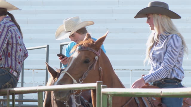 cowgirls on their cellphones waiting to compete - cowgirl stock videos & royalty-free footage
