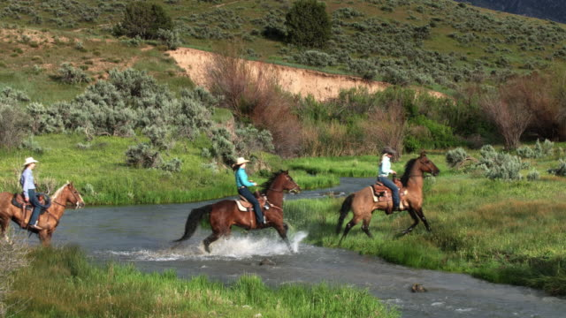 Cowgirls Riding Through River