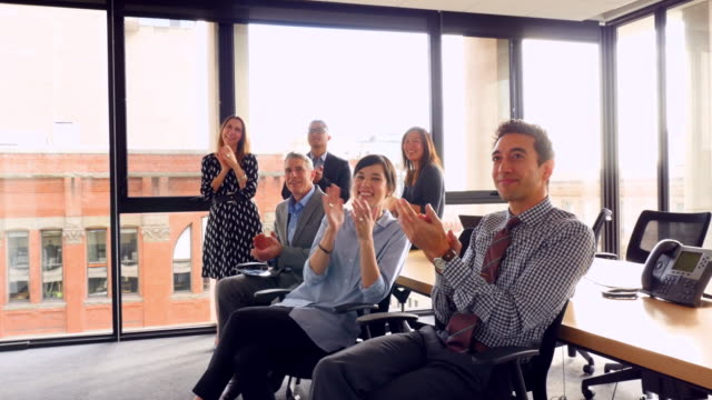 PAN ZI Coworkers applauding after presentation in office conference room