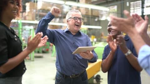 kollegor firar några goda nyheter i en fabrik - framgång bildbanksvideor och videomaterial från bakom kulisserna