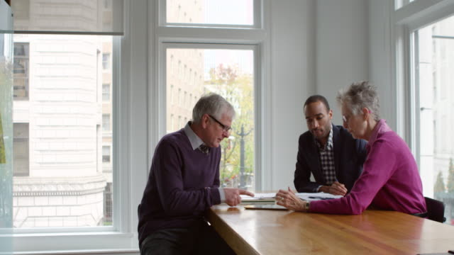 vídeos de stock, filmes e b-roll de ms coworkers discussing project on digital tablet in office - grupo pequeno de pessoas