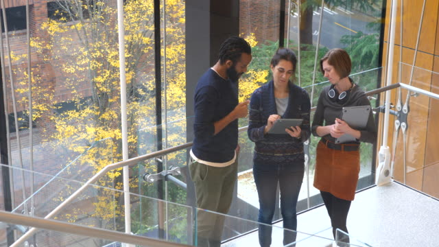ms coworkers discussing project on digital tablet on stairs of office building - 30 39 years stock videos & royalty-free footage