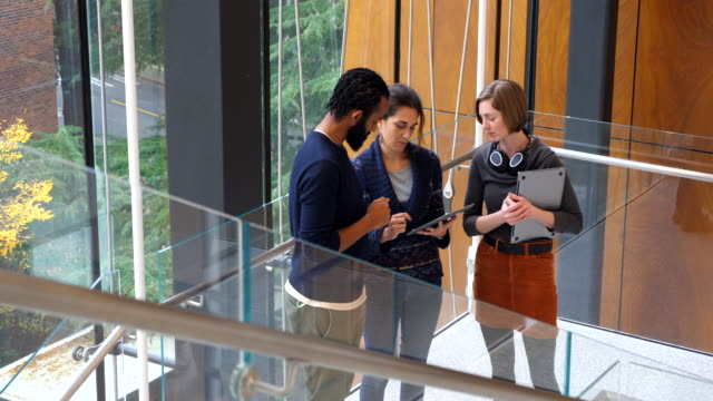 pan coworkers discussing project on digital tablet on stairs of office building - university of washington stock videos & royalty-free footage