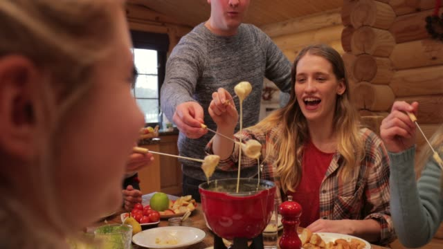 coworkers eating fondue - capanna di legno video stock e b–roll