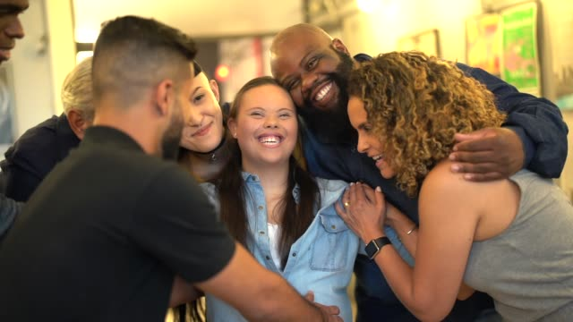 vídeos de stock e filmes b-roll de coworkers embracing a special businessperson at workplace - multi ethnic group