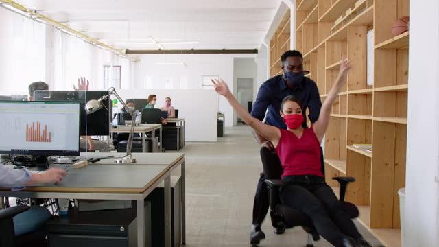 stockvideo's en b-roll-footage met medewerkers die pret in bureau tijdens pandemie hebben - bureaustoel