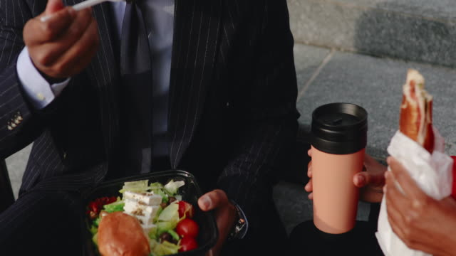 coworkers having lunch break outdoors - lunch break stock videos & royalty-free footage