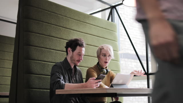 coworkers in a meeting looking at a digital tablet - mobilio video stock e b–roll