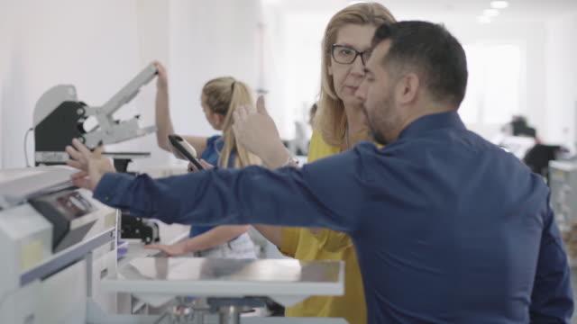 vídeos de stock e filmes b-roll de coworkers in printing factory - fábrica de impressão