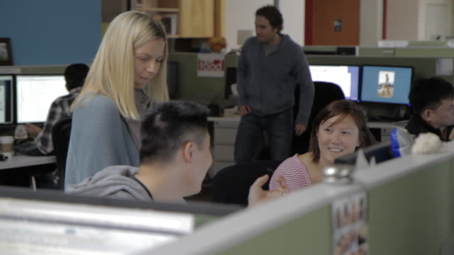 co-workers laugh & joke at their workspace - candid stock videos & royalty-free footage