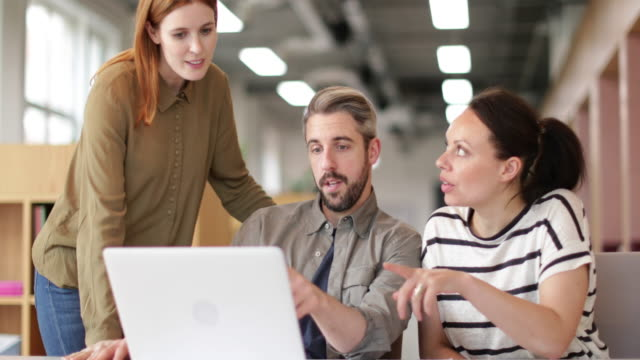 vídeos de stock, filmes e b-roll de coworkers looking at a laptop together - vanguardista