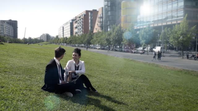 vídeos y material grabado en eventos de stock de co-workers meet in urban park for work - vestimenta de negocios formal
