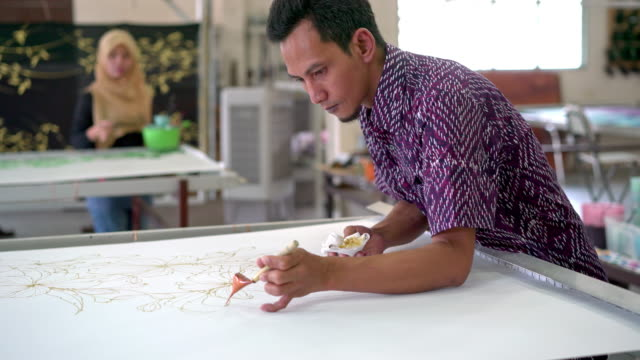 coworkers painting in a batik workshop - malaysia stock videos & royalty-free footage