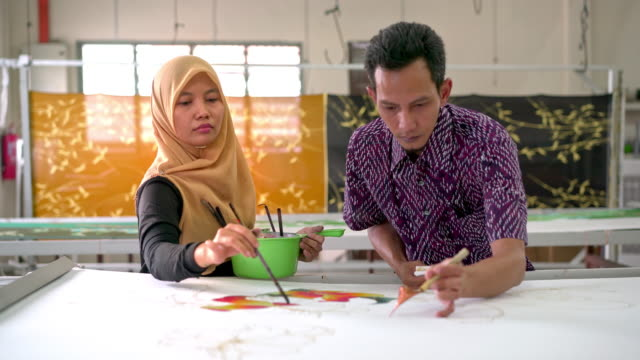 coworkers painting in a batik workshop - batik stock videos and b-roll footage