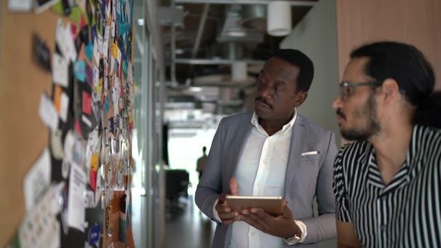 vidéos et rushes de collègues de planification avec tablette numérique ayant de nouvelles idées près du tableau d'affichage au travail - panneau d'information