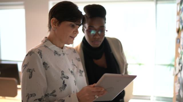 vídeos y material grabado en eventos de stock de compañeros de trabajo que planean con tableta digital teniendo nuevas ideas cercanas al tablón de anuncios en el trabajo - dedicación