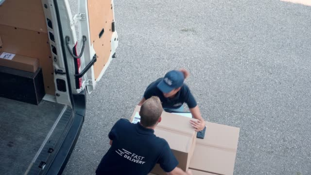 coworkers rushing to load packages in a delivery van - van stock videos & royalty-free footage