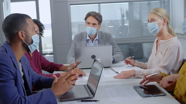 co-workers sitting in the meeting room and working while wearing protective masks - small group of people stock videos & royalty-free footage