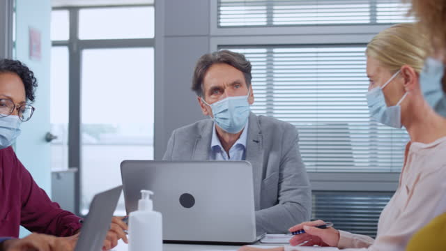 ds co-workers sitting in the meeting room and working while wearing protective masks - health and safety stock videos & royalty-free footage