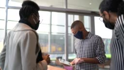 Coworkers talking and using digital tablet on office's lobby - with face mask