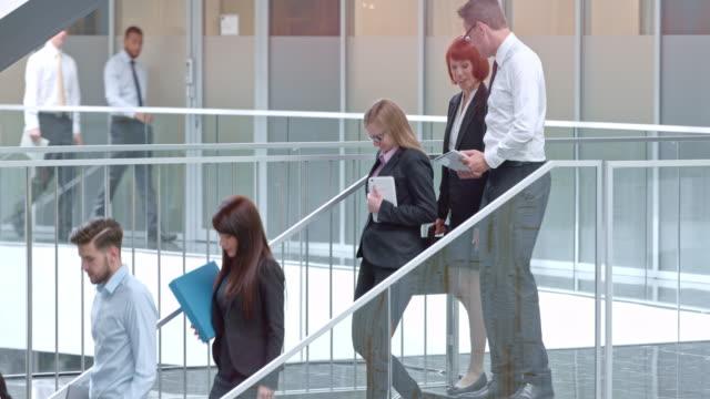 DS compañeros de trabajo hablar mientras caminaba por la escalera