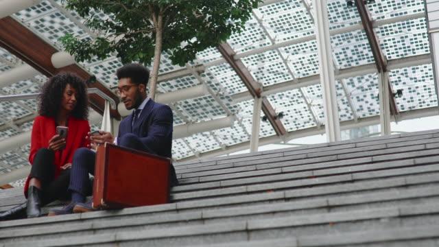階段に座りながら携帯電話を使う同僚 - パルド人点の映像素材/bロール