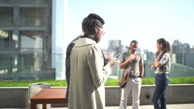 mitarbeiter zu fuß und mit handy auf terrasse büro dach - patio stock-videos und b-roll-filmmaterial