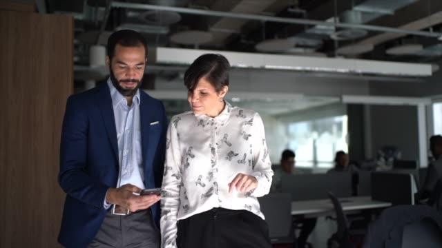 stockvideo's en b-roll-footage met medewerkers die en mobiele telefoon op het werk lopen en gebruiken - advies