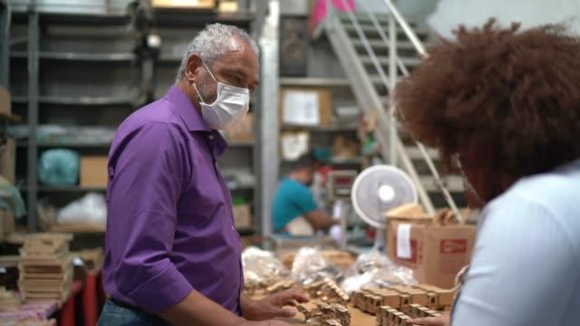 vídeos de stock e filmes b-roll de coworkers wearing face mask and working at craft warehouse - trabalhador de armazém