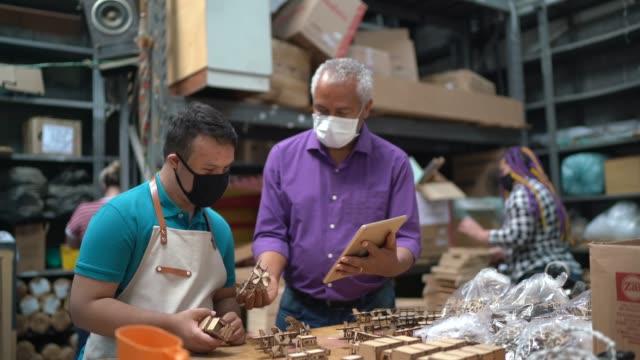 vidéos et rushes de collègues portant le masque facial et travaillant utilisant la tablette à l'entrepôt d'artisanat - artisanat