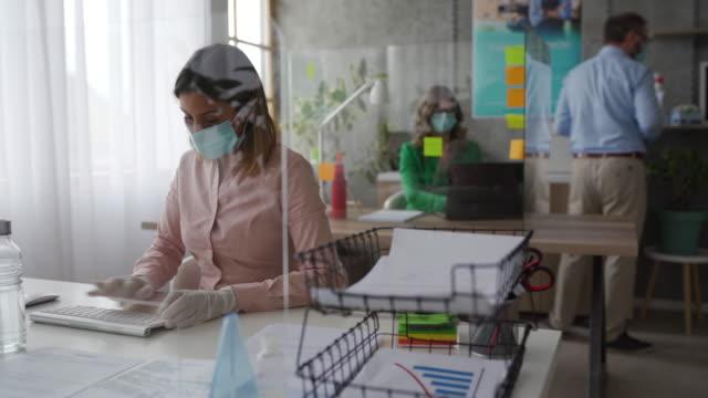 mitarbeiter mit schützenden gesichtsmasken mit computer in bankfiliale - arbeitssicherheit stock-videos und b-roll-filmmaterial