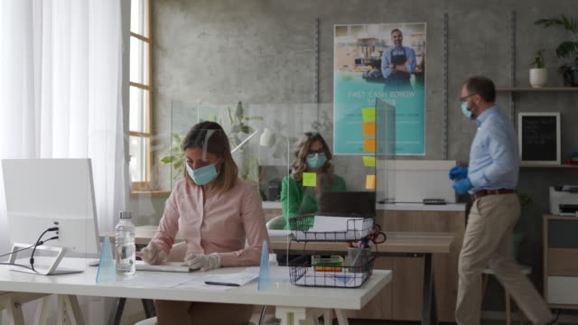 coworkers with protective face masks using computer in bank office - safety stock videos & royalty-free footage