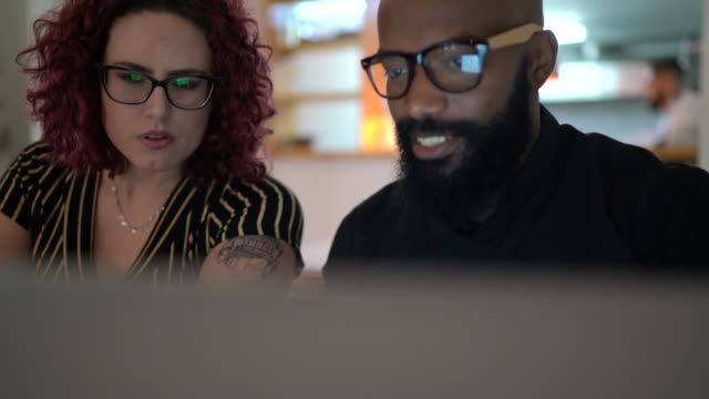 coworkers working together and using laptop in a restaurant - smart casual stock videos & royalty-free footage