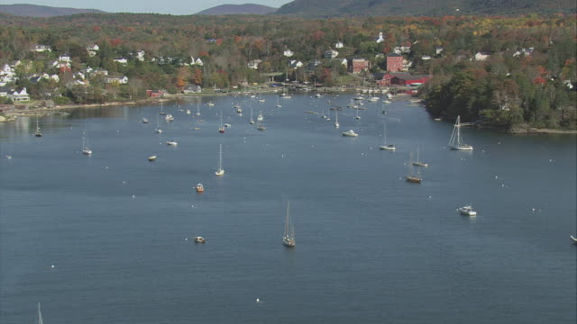 AERIAL Cozy bay dotted with anchored sailboats, heavily wooded hills with town among trees / Rockport, Maine, United States
