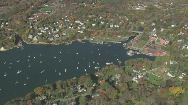 aerial cozy bay dotted with anchored sailboats, heavily wooded hills with town among trees / rockport, maine, united states - rockport maine stock videos & royalty-free footage