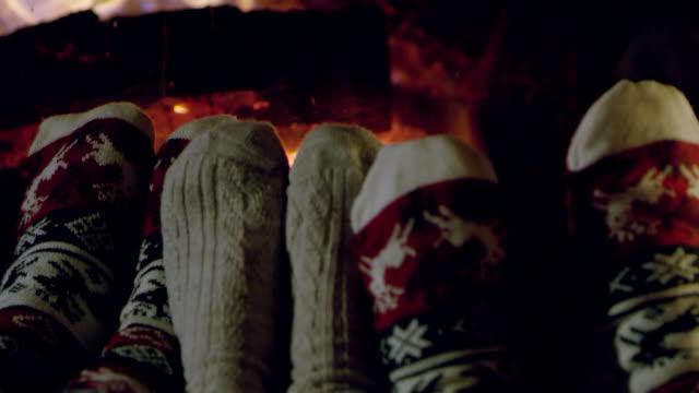 4 k gemütliche füße in weihnachten socken kamin, slow-motion - paar gruppierung stock-videos und b-roll-filmmaterial